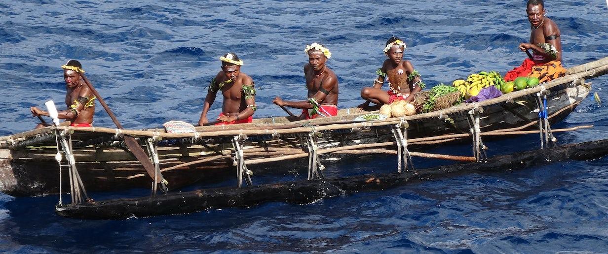Tribal men sailing canoe on the beach at Kitava Island, Papua New Guinea. © Pixabay