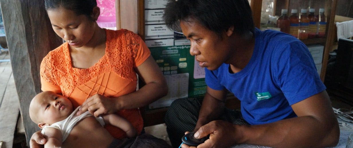 Malaria volunteer sits with mother and young child, iCCM Myanmar